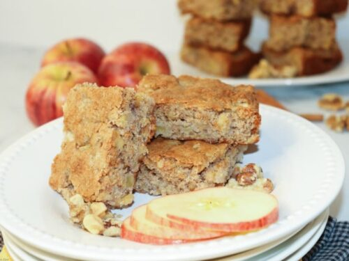 Apple Nut Brownies shown on a stack of white plates with apples on the side.