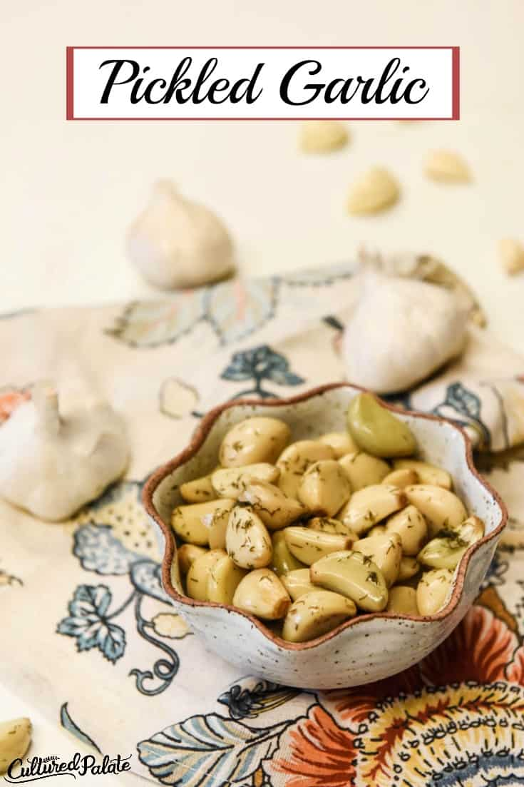 Pickled Garlic shown in bowl with napkin and garlic cloves around.