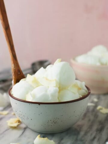 Coconut Ice Cream shown in a bowl with a wooden spoon on a marble table.