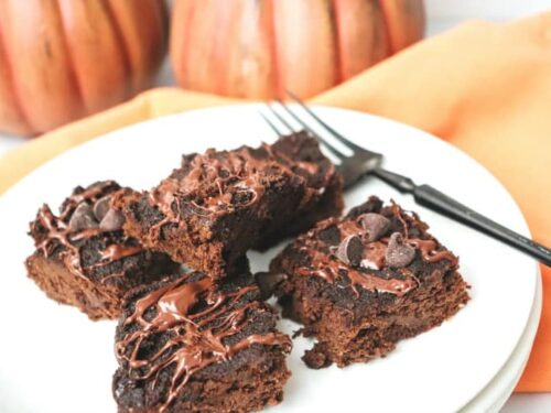 Grain free pumpkin brownies shown on white plate.