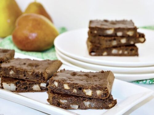 Pear brownies shown on a platter with pears in the background.