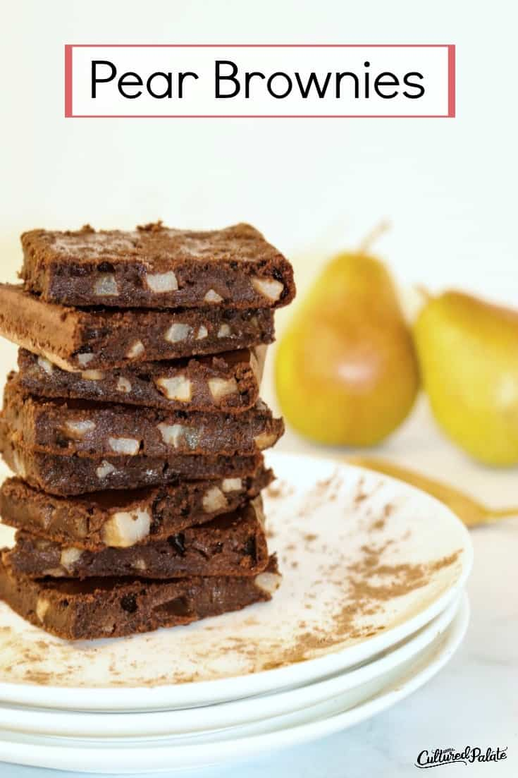 Pear brownies shown stacked on a white plate with pears in the background