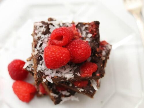 Raspberry Coconut Brownies shown on glass plate with fresh raspberries on top.