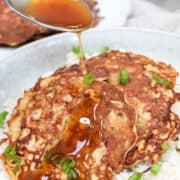 Egg Foo Young pancakes over rice in a bowl with gravy on top