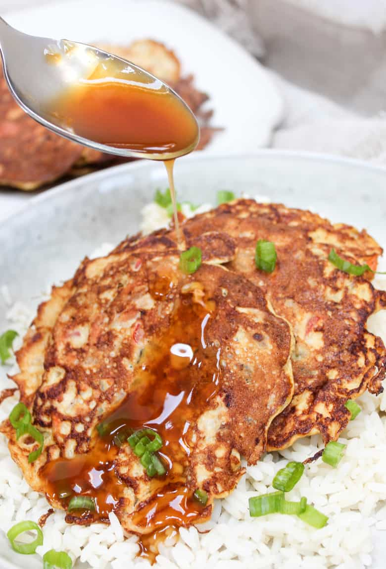 Egg Foo Yound pancakes over rice in a bowl with gravy on top