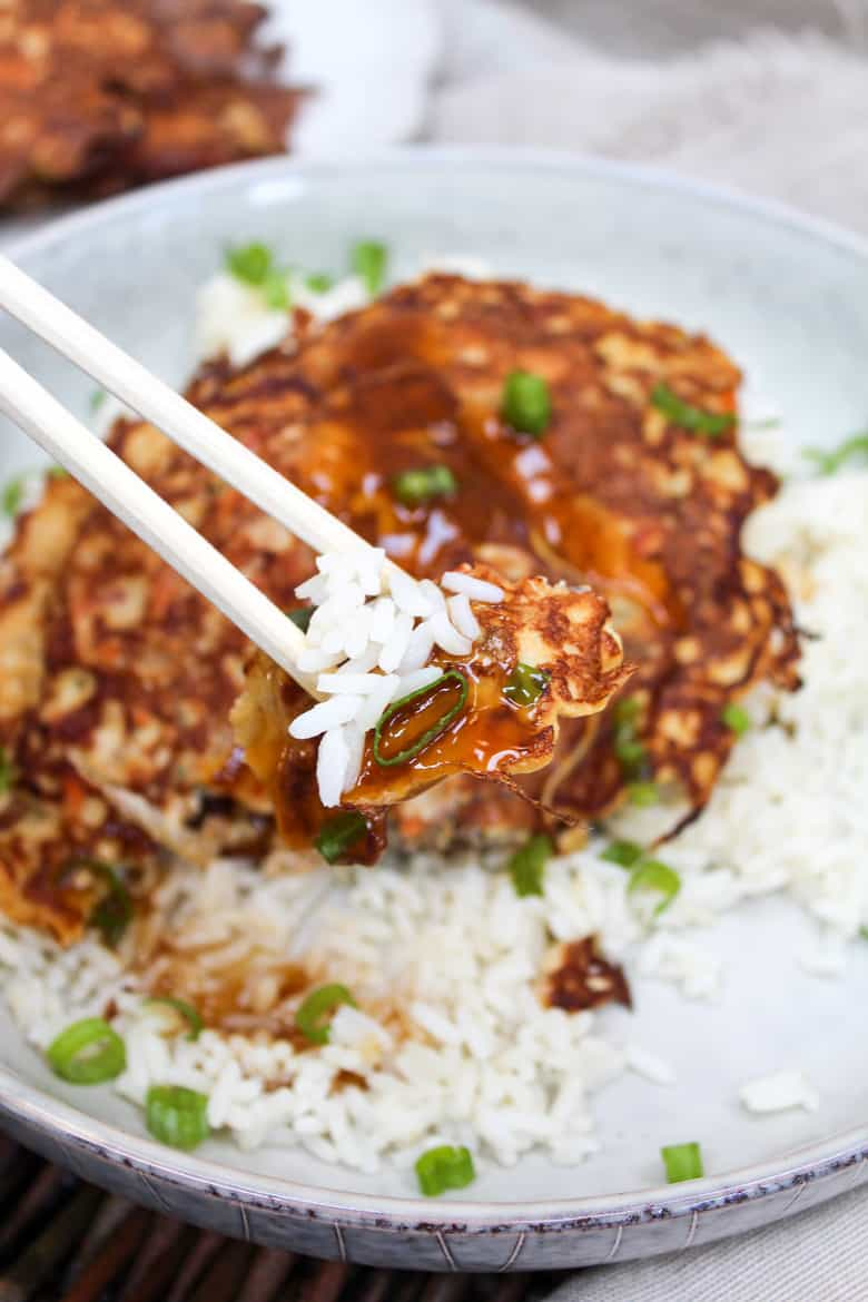 Egg Foo Young pancakes over rice in a bowl with gravy and eaten with chopsticks